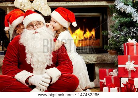 Santa Claus sitting at Christmas tree and listening to two children whispering in his ears