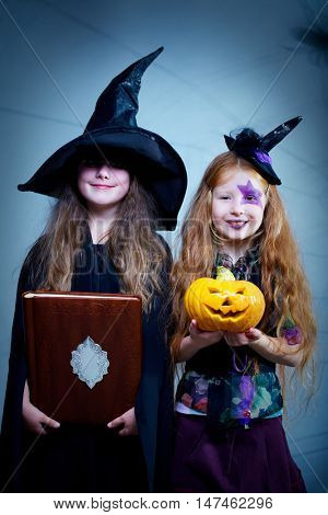 Two little girls in Halloween costumes, one of them holding a book and the other with a pumpkin, looking at camera and smiling