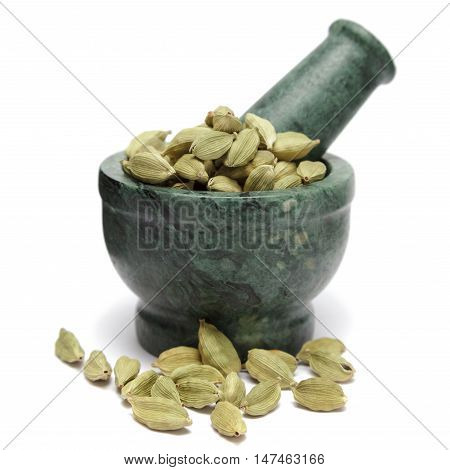 Organic Green or True cardamom (Elettaria cardamomum) on marble pestle and over white background.