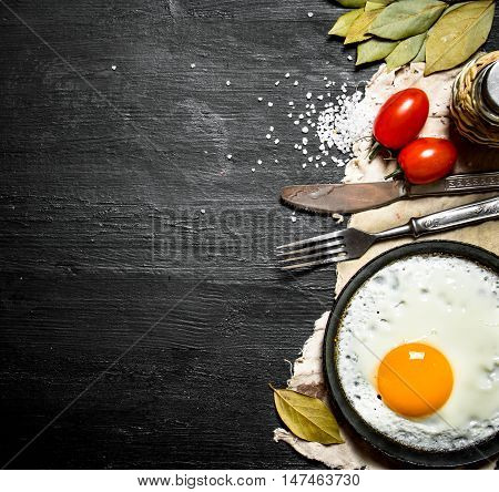 Fried egg with tomatoes and salt. On a black wooden background.