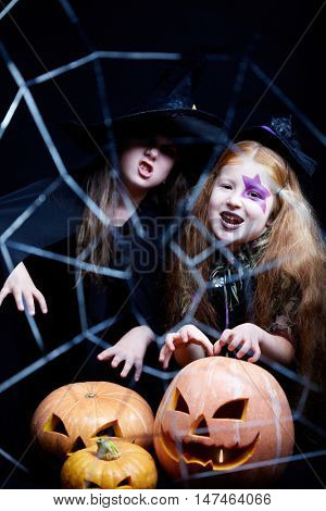 Two girls dressed in witches conjuring over pumpkins, looking at camera and grimacing behind the cobweb