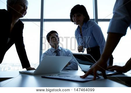 Black put image of four successful business people at work