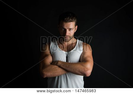 young handsome bearded man, sexy, macho with muscular hands and beard on serious face in white vest posing in studio on black background