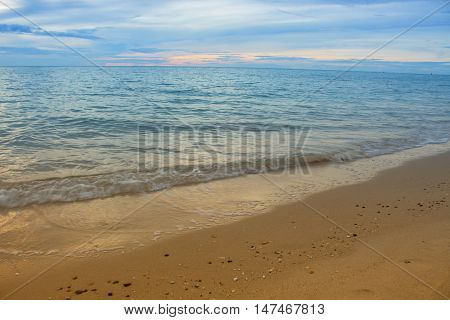 Sea water and beach and sky. Cold Warm Filter look Colorful. with lighting reflect in the sunrise morning. : Select focus with shallow depth of field Soft focus noise and grain due long exposure. with copy space.