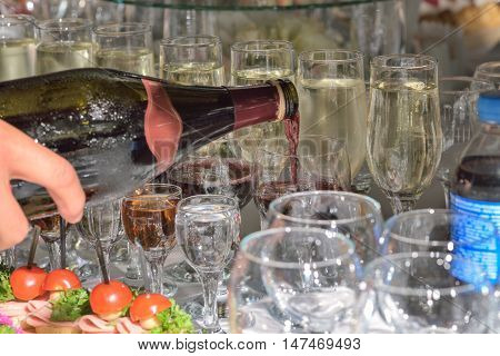 Waiter pour wine in the glass on holiday reception table taken closeup.