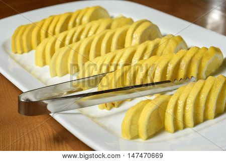 Lemon sliced on a white plate with tongs to feed