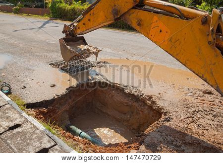 Excavator, bulldozer work a hole the repair of pipe water and sewerage on road