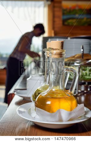 two types of olive oil in carafes on background buffet table