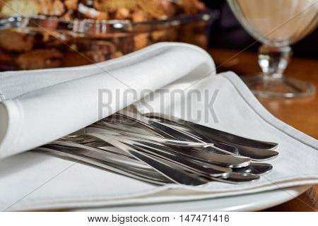 Cutlery - spoons, forks and knives in a luxurious table, covered with a white tablecloth. Serving the holiday feast to eat. Luxury Banquet in the restaurant.