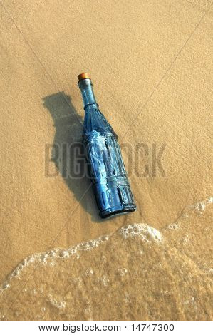 Message in a vintage blue bottle on a sandy shore