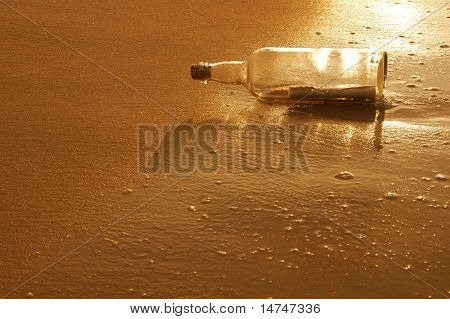 Message in a bottle on a sandy shore at sunset