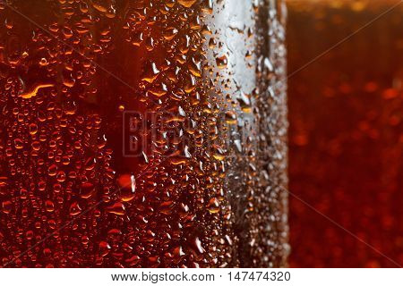 Beer background macro flowing drops on the glass with bubbles brown ale.