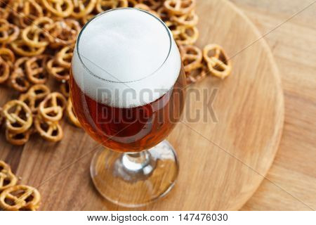 A glass of cold foamy beer with pretzels. Traditional german Oktoberfest snacks and drink on wooden background
