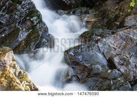 River is flowing down through rocks. Small waterfall in the mountains.