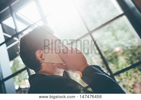 Man on the phone. Low angle view of young man talking on the mobile phone and looking away while standing in front of the big window indoors