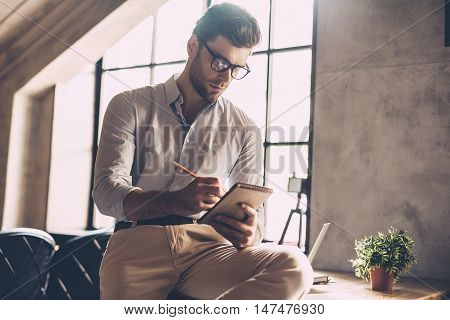 Just inspired. Confident young man in smart casual wear writing something in his notebook while leaning at the desk in office