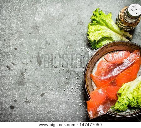 Thin slices of salted salmon with herbs and salt. On a stone background.