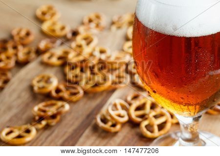 Glass of cold foamy beer with brezel. Traditional german Oktoberfest snacks and beer on wooden background