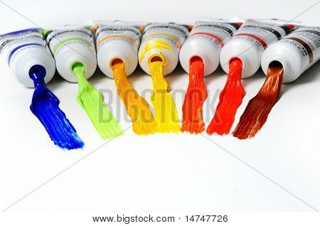 Paint tubes with different colors spread over a white surface