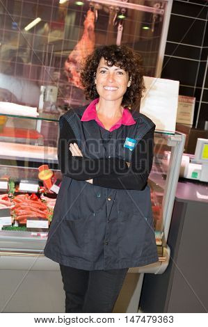 a Confident and smiling supermarket employee standing