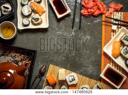 Japanese food. Fragrant tea , sushi and rolls with pickled ginger and soy sauce.