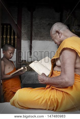 LUANG PRABANG LAO PDR - August 2011: Old monk teaching dhamma to young novice monk at temple in Luang Prabang, Laos
