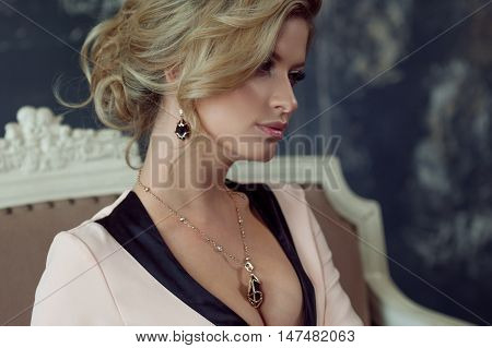 Fashion model with blond hair. Young attractive woman, siting on the sofa, vintage style, close-up