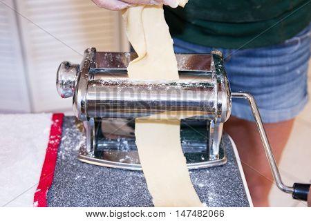 Pasta roller flattening pasta to make Ravioli