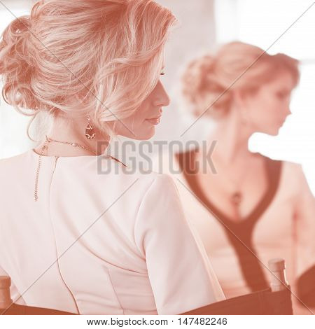Fashion model with blond hair. Young attractive woman, stylish. Attractive woman in evening dress, the reflection in the mirror in the background, pink toned
