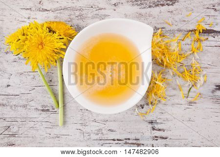 Dandelion honey background herbal remedy. Dandelion flower and stem and honey in bowl top view.