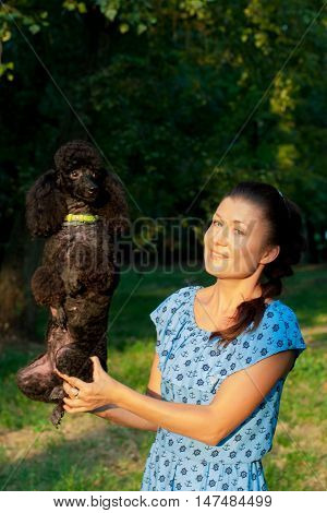 girl holds her hand on a black poodle in nature summer day