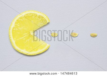 Creative concept photo of a lemon slice eating seeds on grey background.