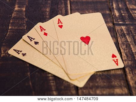 Golden playing cards four aces on wooden board. Playing table