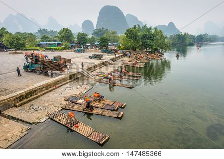 Yangshuo China - October 20 2013: Bamboo rafts on the Li river in the rainy weather (overcast nasty). Thousands of tourist visit yangshuo region in order to admire karst scenery and have Li river cruise in Yangshuo China.