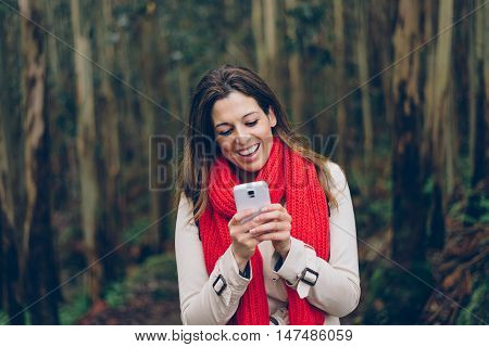 Happy Woman Texting On Smartphone During A Trip To The Forest