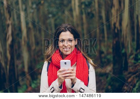 Woman Texting On Smartphone During A Trip To The Forest