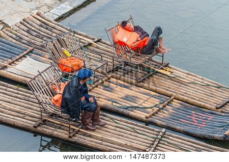 Yangshuo China - October 20 2013: Boaters rest waiting for tourists on their bamboo raft on the bank of the Li River Yangshuo China.