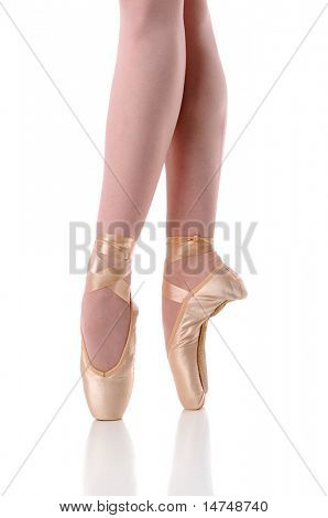 Ballerina's feet dancing on pointe isolated over a white background