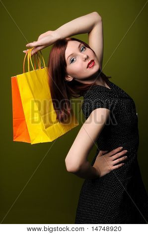 Beautiful redheaded woman posing with shopping bags