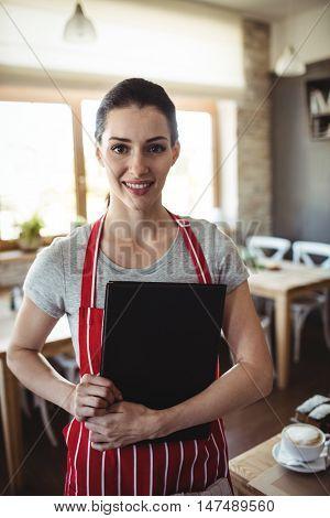 Portrait of female baker holding menu in bakery shop