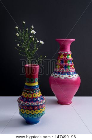 Still life of two artistic painted colorful handcrafted pottery vases little green branches and small white flowers with harsh shadow on white table and black wall