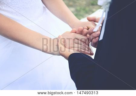 Fiancee and fiance holding hands, closeup