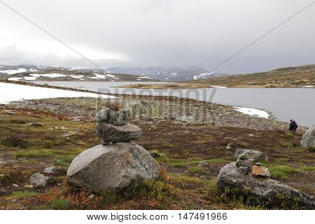 This is the Hardangervidda National Park in Norway in foggy weather. That hand-made stone structures symbolize the legend of the