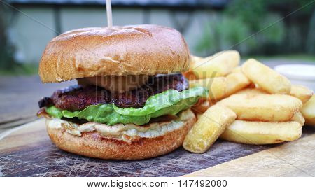 Close up of meat burger with green lettuce relish in a wheat bun offered on wooden board accompanied by chunky potato fries served al fresco in a country pub garden