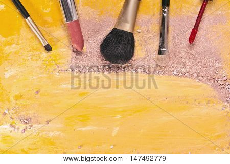 Makeup brushes and lipstick on a vibrant golden yellow background, with traces of powder and blush on it. A horizontal template for a makeup artist's business card or flyer design, with copyspace