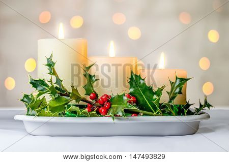 Three descending lit candles with Christmas holly berries and bokeh fairy light background.