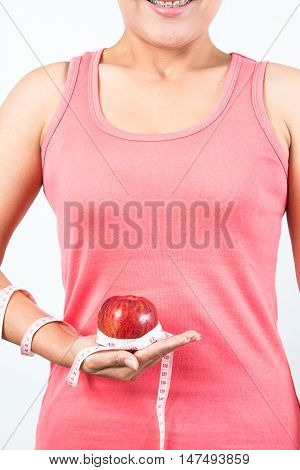 asian woman measuring waist as she holds apple in fitness studio