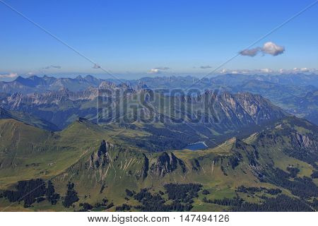 View from Sex Rouge Swiss Alps. Mountain ranges and lake Arnensee. Summer scene.