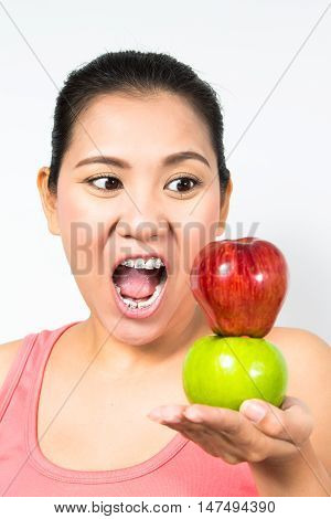 asian woman holding red apple and green apple