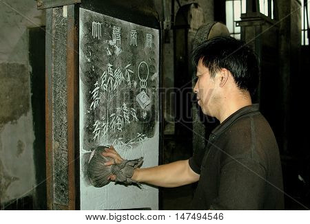 Xi'an China - September 9 2006: Artist using a tamping cloth to create a paper rubbing from Stone Forest tablet at the Bei Lin Museum